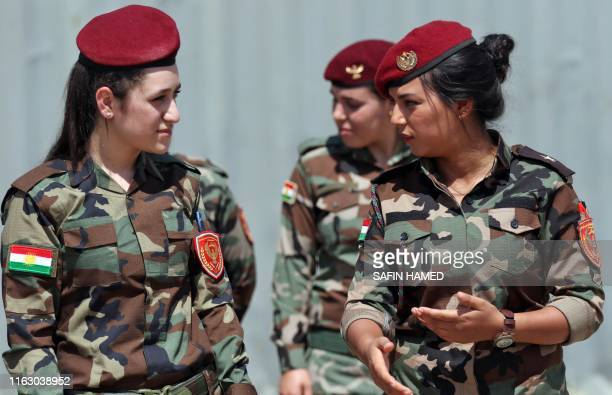 Iraqi Kurdish Peshmerga women fighters speak together during a training session by German military officers during the German Defence Minister's...