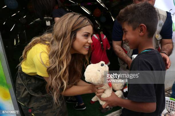 Iraqi Kurdish pop singer Dashni Murad known as the Shakira of Kurdistan offers a teddy bear to a displaced boy during a visit at the alKhazar camp in...