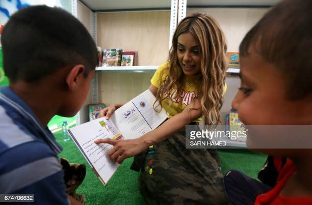 Iraqi Kurdish pop singer Dashni Murad known as the Shakira of Kurdistan reads a book with displaced children during a visit at the alKhazar camp in...