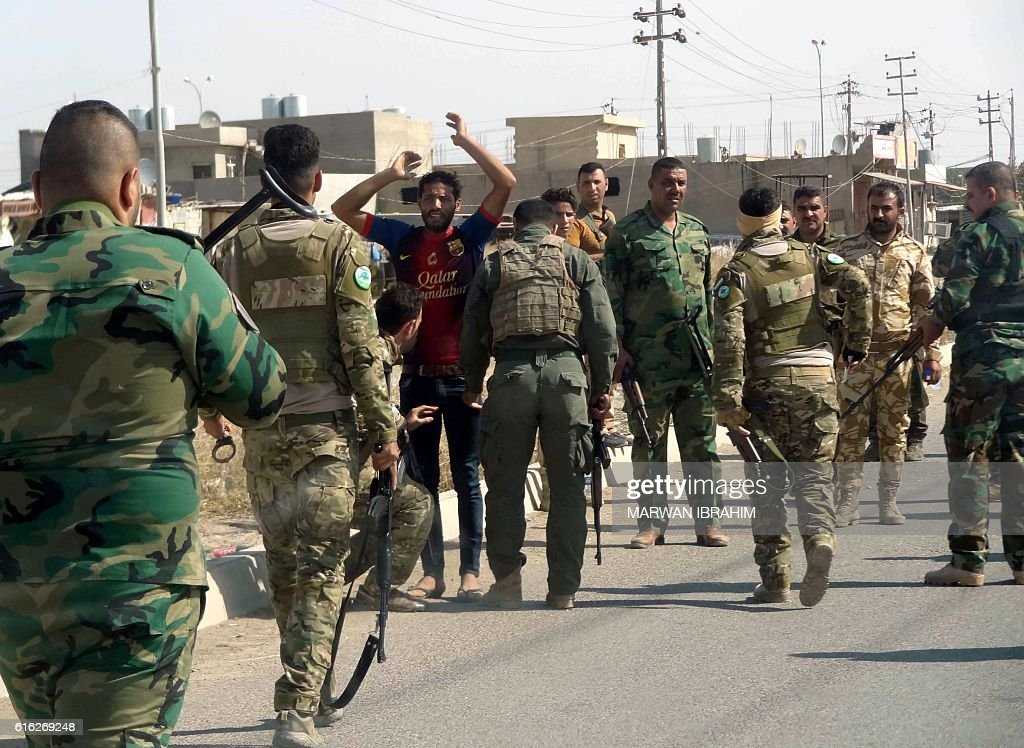Iraqi Kurdish security forces detain a suspected member of the Islamic State (IS) group as they patrol the eastern suburbs of Kirkuk on October 22, 2016, after jihadist gunmen attacked the city. Security forces battled for a second day with Islamic State gunmen who infiltrated Kirkuk in a brazen raid that rattled Iraq as it ramped up an offensive to retake Mosul. / AFP / Marwan IBRAHIM