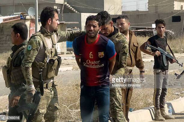 TOPSHOT Iraqi Kurdish security forces detain a suspected member of the Islamic State group as they patrol the eastern suburbs of Kirkuk on October 22...