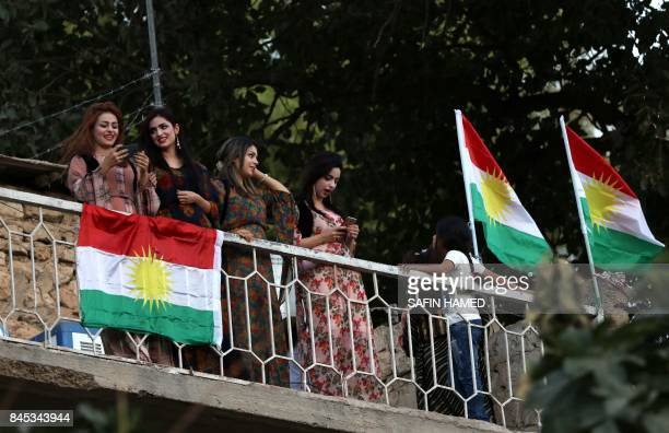 Iraqi Kurdish woman stand next to Kurdish flags during a gathering to show support for the upcoming independence referendum and encourage people to...