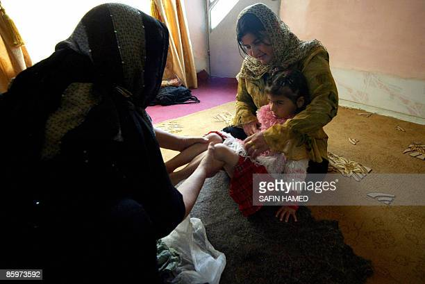 Iraqi Kurdish women prepare fouryearold Shwen for circumcision in Suleimaniyah on April 14 2009 The parliament in Iraq's northern autonomous region...