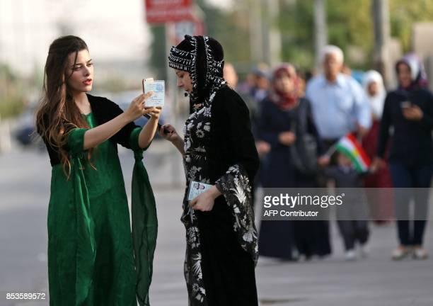 Iraqi Kurdish women uses their cellphones as they hold on to their IDs while arriving to cast their votes in the referendum on independence at a...