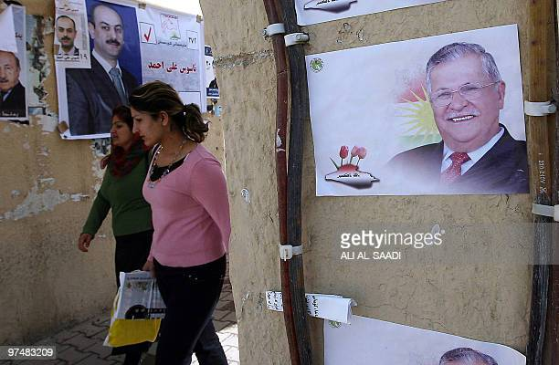 Iraqi Kurdish women walk past campaign posters for parliamentary candidates and President Jalal Talabani in the northern city of Sulaimaniyah on...