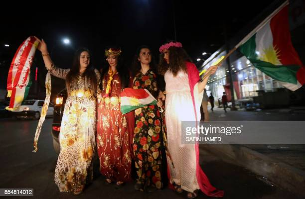 Iraqi Kurdish women wave the Kurdish flag as they celebrate the independence referendum in the streets of the northern city of Arbil on September 27...