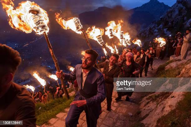 Iraqi Kurds carry lit torches up Kali mountain to celebrate Nowruz, the Persian new year, on March 20, 2021 in Akre, Iraq. The Persian New Year is an...