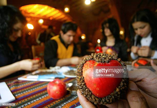 Iraqi Kurds decorate apples with cloves to offer to their partners on Valentine's Day at a restaurant in the Kurdish city of Arbil in northern Iraq...