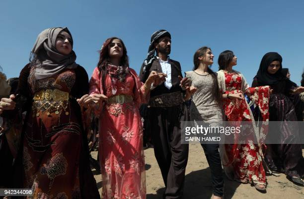 Iraqi Kurds dressed in traditional clothing dance in a cultural festival near Maqlub Mountains 30 km northeast of Mosul on April 5 2018