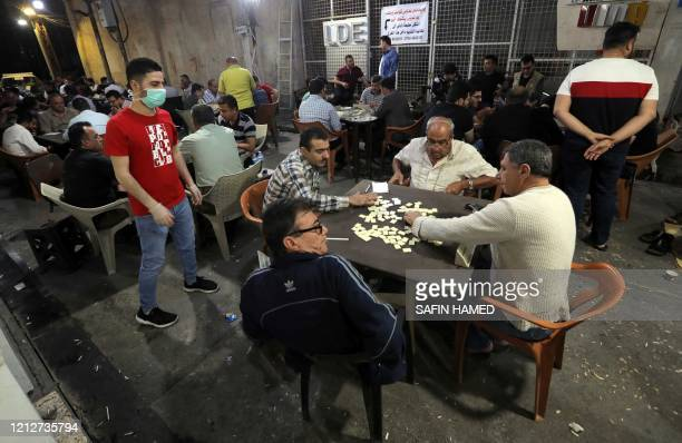 Iraqi Kurds gather in a popular market area after sunset to eat and play traditional games, including cards and dominoes, in Arbil, the capital of...