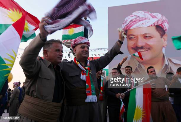 Iraqi Kurds gather in the street waving Kurdish flags next to a poster of the president of Iraq's Kurdistan region as they urge people to vote in the...