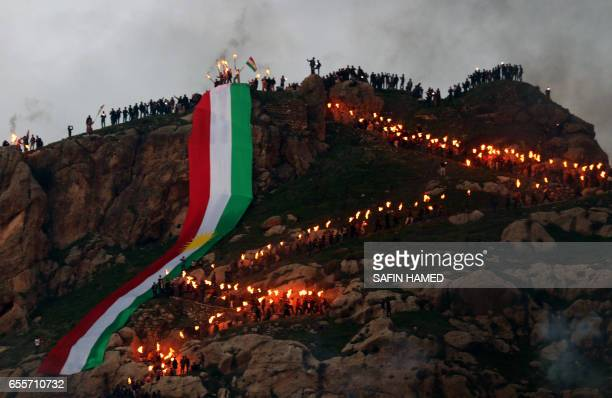 Iraqi Kurds holding lit torches walk up a mountain, draped in a large Kurdish flag, in the town of Akra, 500 km north of Baghdad, on March 20, 2017...