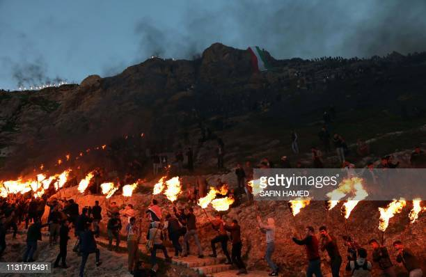TOPSHOT Iraqi Kurds holding lit torches walk up a mountain in the town of Akra 500 kilometres north of Baghdad on March 20 2019 during celebrations...