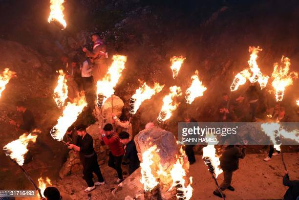 Iraqi Kurds holding lit torches walk up a mountain in the town of Akra 500 kilometres north of Baghdad on March 20 2019 during celebrations of Nowruz...
