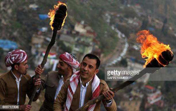 Iraqi Kurds holding lit torches walk up a mountain in the town of Akra 500 km north of Baghdad on March 20 2017 as they celebrate the Noruz spring...