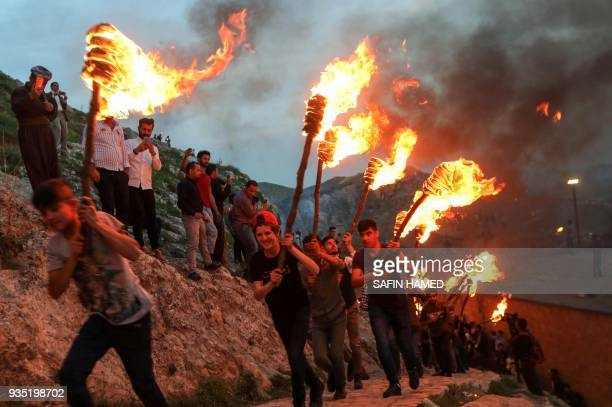 Iraqi Kurds holding lit torches walk up a mountain in the town of Akra 500 kilometres north of Baghdad on March 20 2018 during celebrations for Noruz...