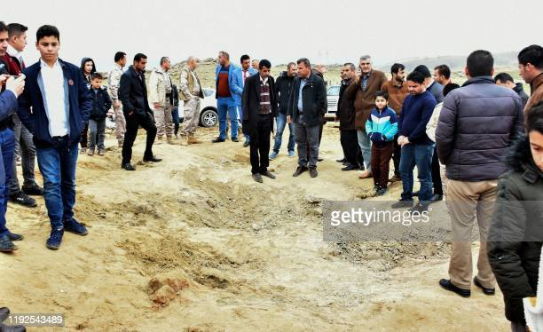 Iraqi Kurds inspect a crater reportedly caused by an Iranian missile initially fired at Iraqi bases housing US and other USled coalition troops in...