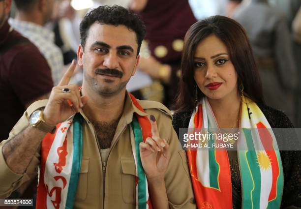 Iraqi Kurds show their inkstained fingers after casting their votes in the Kurdish independence referendum in the city of Kirkuk in northern Iraq on...