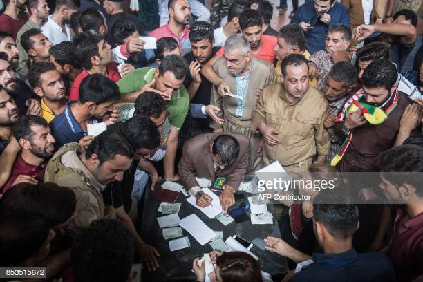 TOPSHOT Iraqi Kurds wait to check their identities before voting in the Kurdish independence referendum at a stadium in Arbil which is being used as...