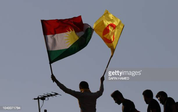 Iraqi Kurds wave flags during an electoral rally for the Kurdistan Democratic Party at the Franco Hariri Stadium in Arbil the capital of the northern...