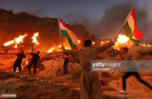 TOPSHOT Iraqi Kurds wave Kurdish flags and hold burning torches as they walk up a mountain during a gathering to show support for the upcoming...
