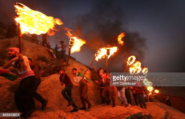 Iraqi Kurds wave Kurdish flags and hold torches as they walk up a mountain during a gathering to show support for the upcoming independence...