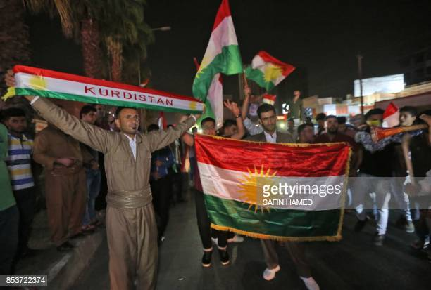Iraqi Kurds wave the Kurdish flag as they celebrate in the streets of the northern city of Arbil on September 25 2017 following a referendum on...
