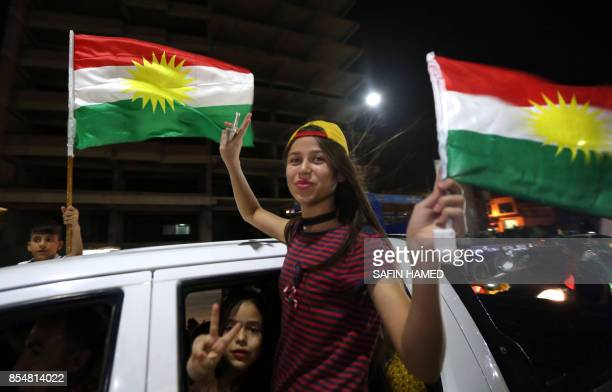 Iraqi Kurds wave the Kurdish flag as they celebrate the independence referendum in the streets of the northern city of Arbil on September 27 2017 in...