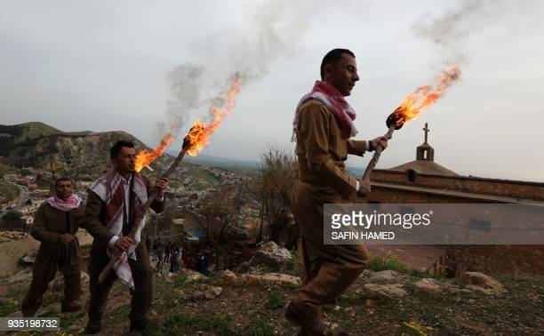 Iraqi Kurds wearing traditional Peshmerga outfits and holding lit torches walk up a mountain in the town of Akra 500 kilometres north of Baghdad on...