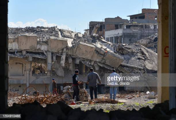 Iraqi labourers recover scrap metal from a destroyed building in the northern Iraqi city of Mosul on March 3, 2020