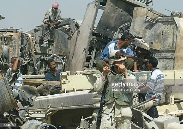 Iraqi looters sit over destroyed vehicles behind a US Army soldier from the 1457 Engineer Battalion standing on guard, while tonnes of scrap metal...