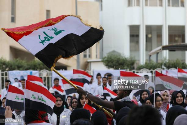 Iraqi medical students wave national flags as they take part in an anti-government protest amid ongoing student strikes at the campus of the...