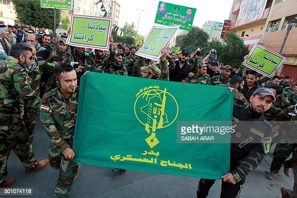 Iraqi members of the Tehranbacked Shiite Badr militia take part in a demonstration in Baghdad's Tahrir Square on December 12 to demand the withdrawal...
