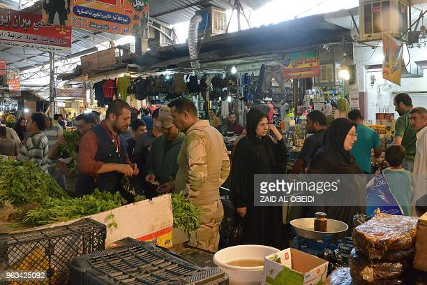 Iraqi men and women buy food in an open air market after breaking the fast during the holy month of Ramadan in Mosul on May 24 2018 The Islamist...