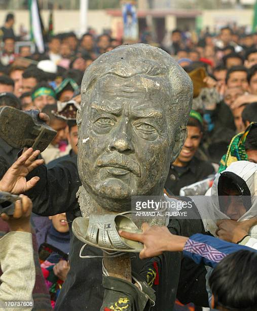Iraqi men beat the head from a broken statue of ousted president Saddam Hussein following Friday noon prayers in Sadr City a predominately Shiite...