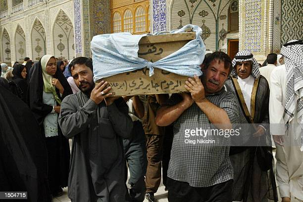 Iraqi men carry a coffin during a funeral ceremony at a mosque named the Shrine of the Imam Ali Ibn Abi Talib October 18, 2002 in the town known as...