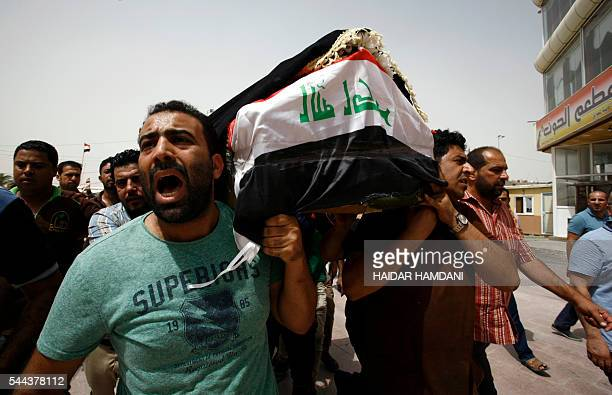 TOPSHOT Iraqi men carry a coffin in the holy Iraqi city of Najaf on July 3 during a funeral procession for the victims of a suicide bombing that...