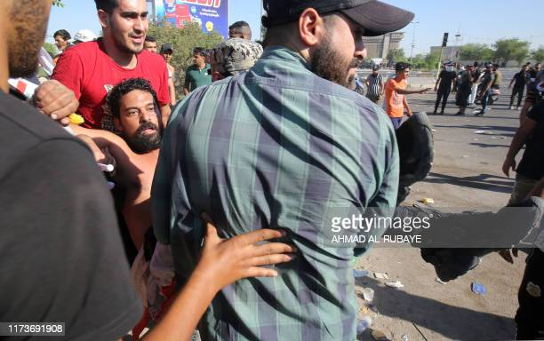 Iraqi men carry away a wounded protester during a demonstration against state corruption failing public services and unemployment in the Iraqi...
