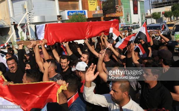 Iraqi men carry the coffin of a demonstrator reportedly killed earlier outside the Iranian consulate, during his funeral in the Shiite shrine city of...