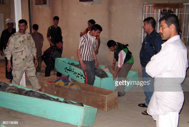 Iraqi men carry the coffins of killed Sunni Awakening members to the morgue of a hospital in the restive city of Baquba northeast of Baghdad on March...