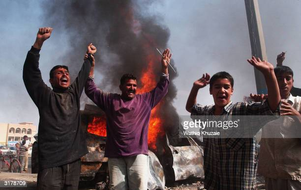 Iraqi men celebrate at the scene of an attack on two civilian vehicles that killed at least four foreign nationals on March 31 2004 in Fallujah Iraq...
