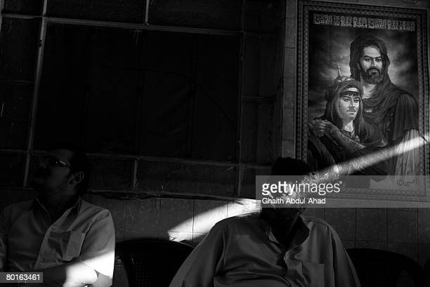 Iraqi men chat and drink tea in an Iraqi cafe under a big poster of Imam Ali March 1in the area of Saida Zainab a predominantly Shia neighborhood on...