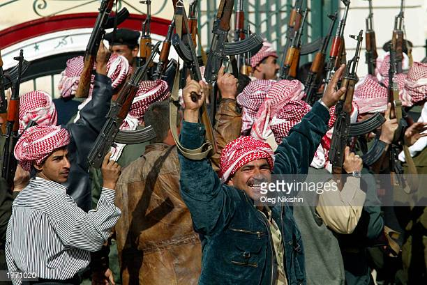 Iraqi men cheer while holding their AK47 rifles after they marched during a parade February 8 2003 in Tikrit Saddam Hussein's hometown Iraq Chief UN...