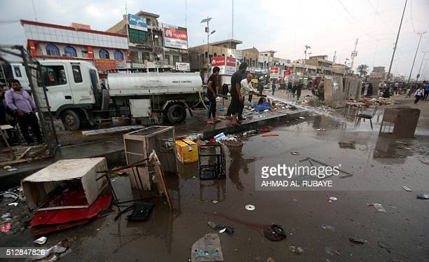 Iraqi men clean up the site following a bombing claimed by the Islamic State group near a market in the Sadr City area of northern Baghdad on...