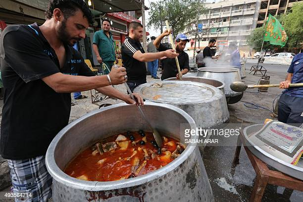 Iraqi men cook large pots of food in Baghdad's Karada district on October 21 2015 as Iraqi Shiite Muslims commemorate Ashura which marks the seventh...