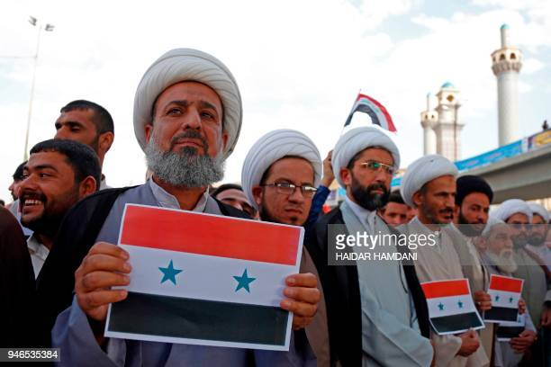 Iraqi men display the syrian flag as they attend the demonstration against the western bombings of Syria on april 15 in Najaf US French and British...