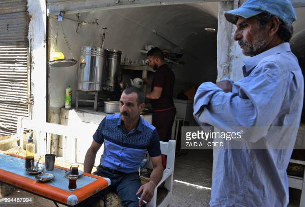 Iraqi men drink tea at a traditional coffee shop in the northern city of Mosul on July 9 2018 Iraqi forces announced the 'liberation' of the...