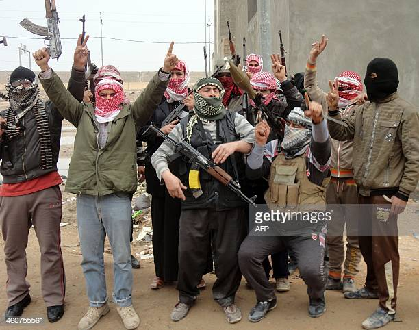 Iraqi men from local tribes brandish their weapons as they pose for a photograph in the city of Fallujah west of the capital Baghdad on January 5...