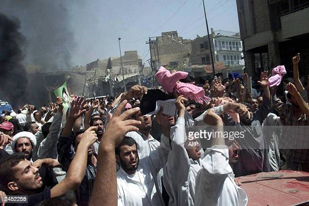 Iraqi men gather at the blast site 29 August 2003 outside the Shrine of Imam Ali one of Shiite Islam's holiest shrines in the central city of Najaf...