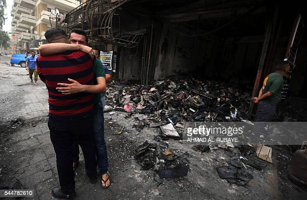 Iraqi men hug on July 4 2016 at the site of a suicidebombing attack which took place a day earlier in Baghdad's Karrada neighbourhood Iraqis mourned...